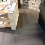 Elegante pavimento in Pvc di basso spessore posato a secco color grigio scuro con rivestimento in pietra. Realizzato da Linealegno Borgosatollo Brescia.
